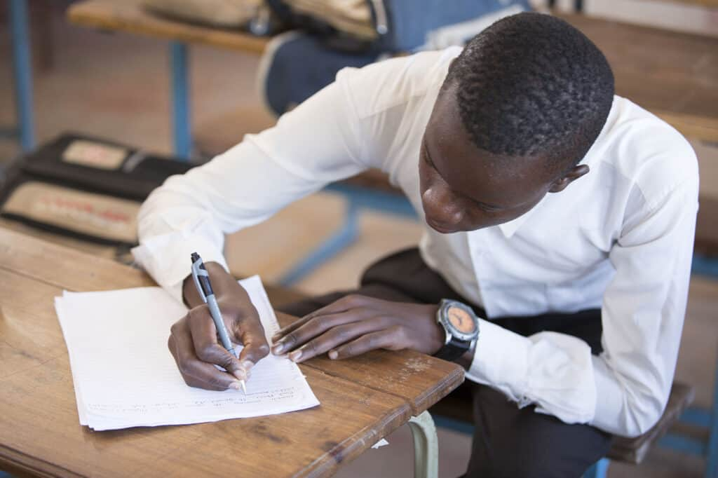 A photo of a pupil in school uniform writing at his desk to illustrate our education support work