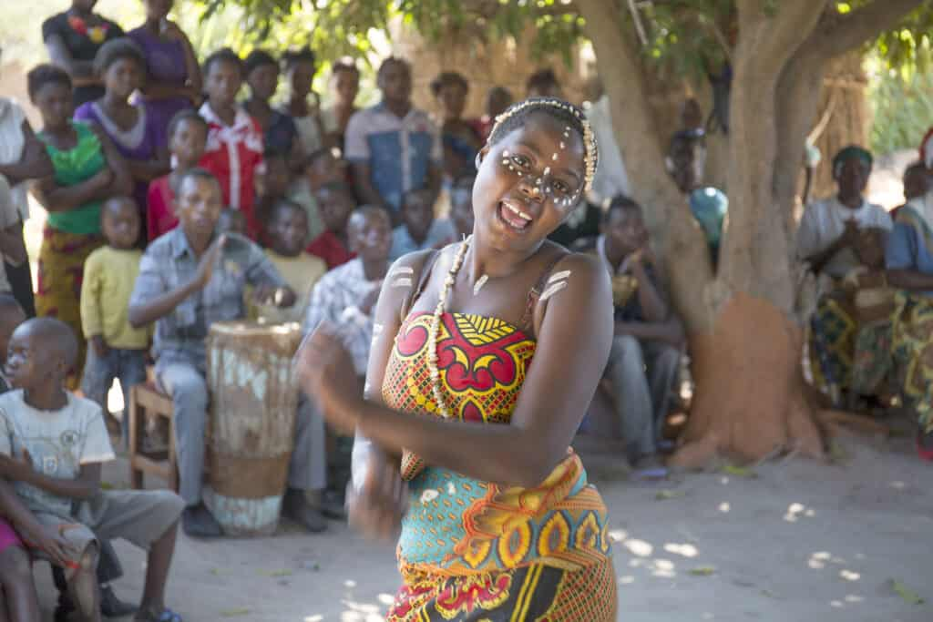 A photo of a girl dancing and singing from Nevers Care and Support Group, a fostering and education project for abandoned orphans and other struggling children