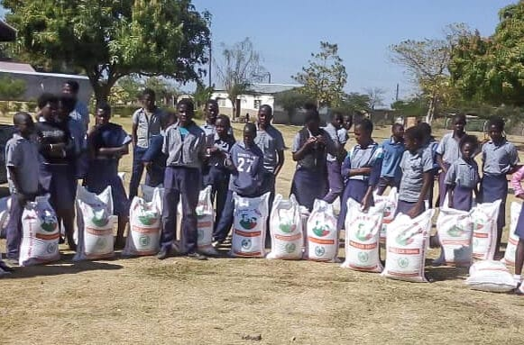 A photo showing school pupils with their sacks of grain, to illustrate our drought response