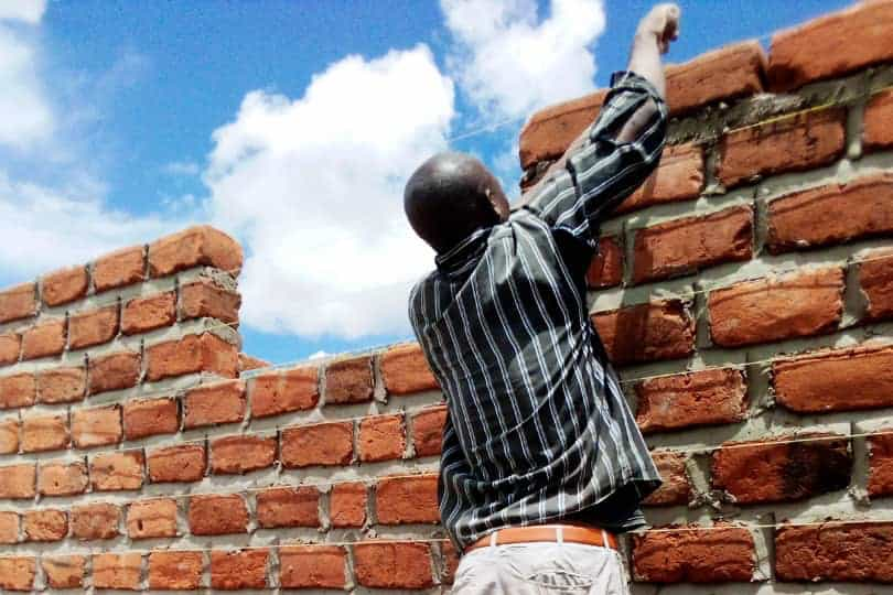 An image showing a man building a wall at the Lubushi girls dormitory we're supporting